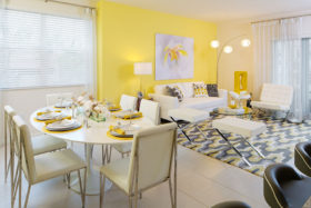 Dining and living room with large rug, modern couch and chairs, and six person dining table with place settings.