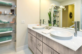 Bathroom with smooth tile floors, dual vanity, and shelves with a selection of towels and soaps.